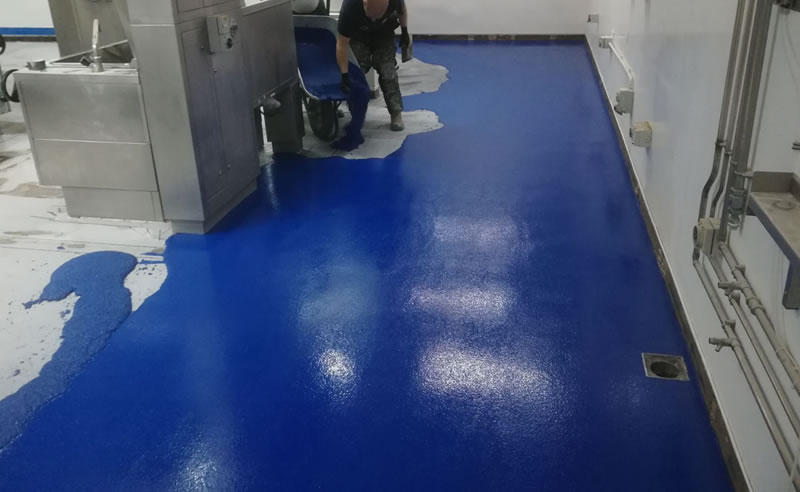 Picture showing the blue heavy duty polyurethane resin flooring being poured onto the prepared floor