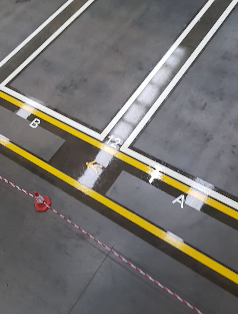 a photo of completed yellow and white lines on a concrete floor in a warehouse