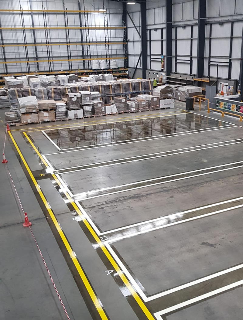 completed demarcation in yellow on a concrete floor in a warehouse