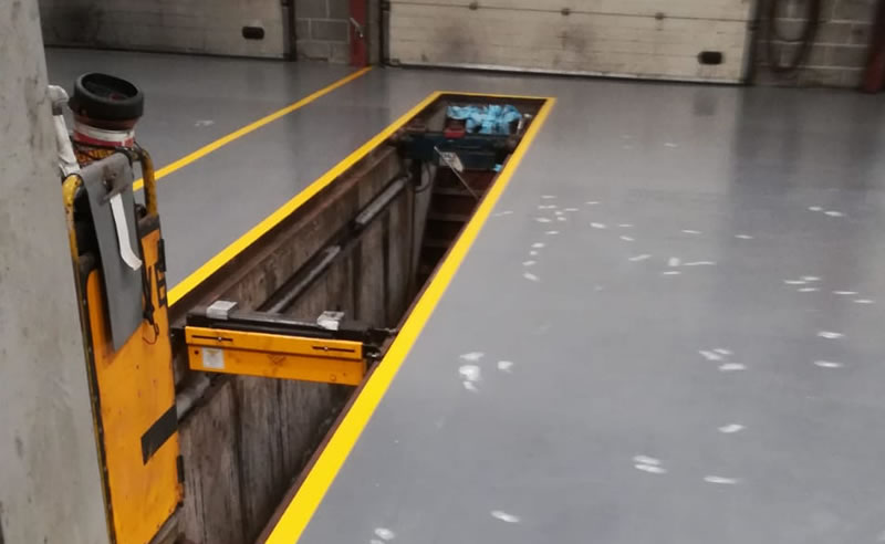 adding yellow demarcation to a finished floor for a car workshop in bristol