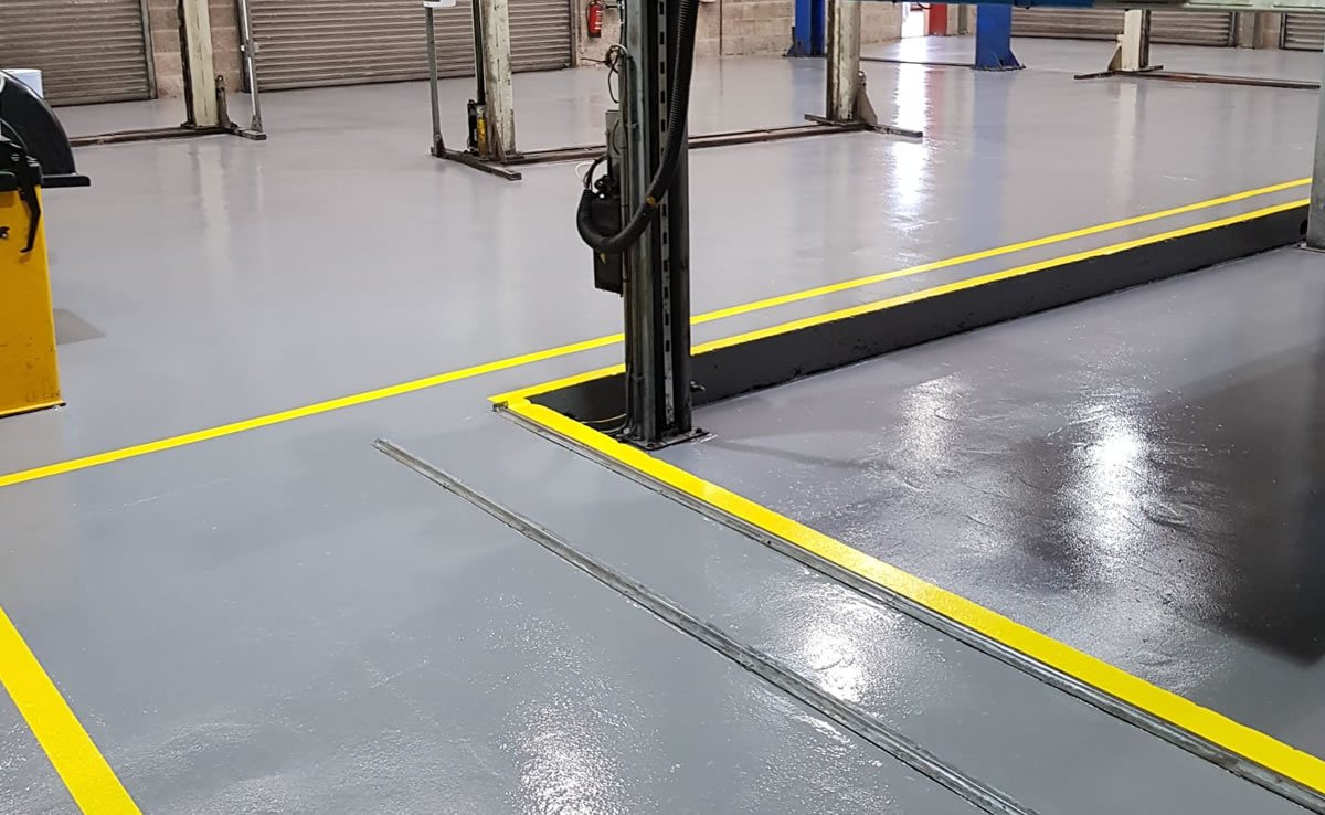 completed resin flooring with yellow lines at a car workshop in bristol