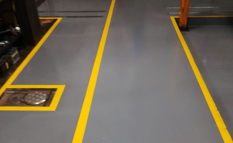 completed yellow demarcation to a floor for a car workshop