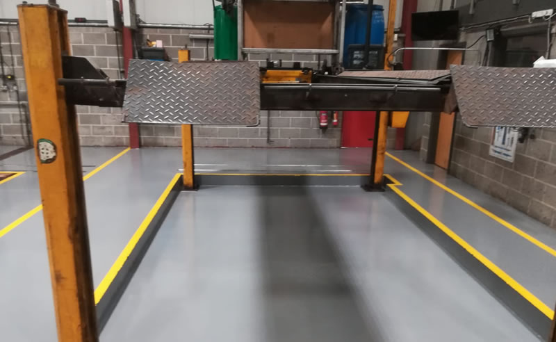 completed yellow demarcation to a resin floor for a car workshop