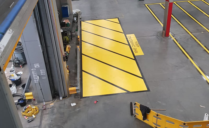 warehouse floor with yellow forklift charging bay
