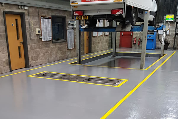 grey floor with yellow markings for a car workshop