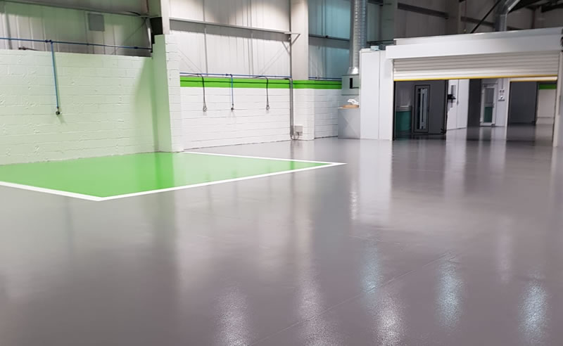 grey resin floor with green area painted on the floor