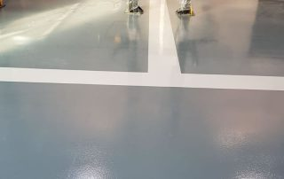 grey resin flooring with white lines for a car dealership