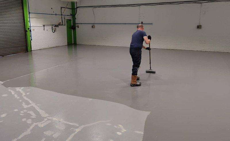 installing grey resin flooring to workshop floor