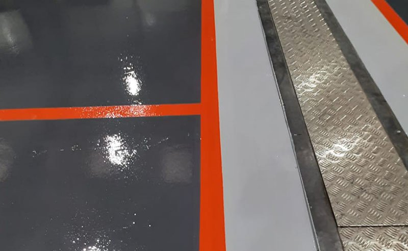 resin flooring in a new automotive workshop in grey and orange